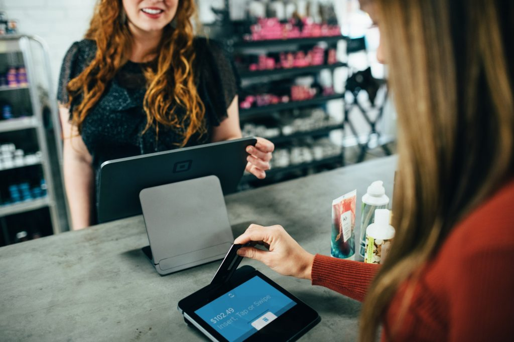 This is the main photograph for the How to accept card payments article. It shows a shopper inserting their payment card into a point of sale terminal.