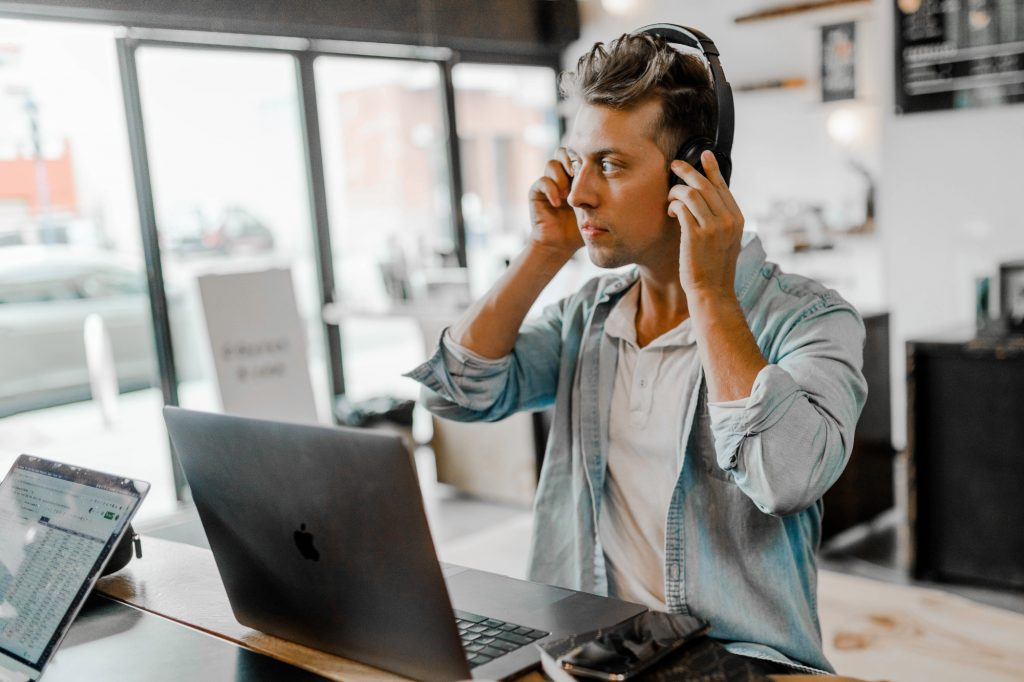 This is the second photograph used in the article What is a business phone system? It shows a man putting on a softphone headset in front of his laptop.